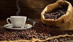 عکس قهوه داغ در فنجان سفید و دانه های قهوه