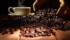 عکس فنجان قهوه داغ و دانه های قهوه