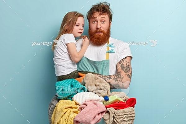 عکس مرد خسته از شستن لباس  و دخترش