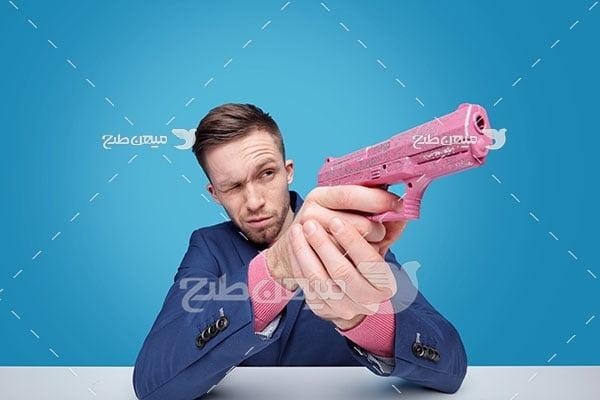 عکس فرد مسلح با کلت صورتی