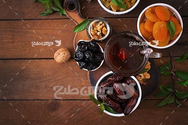 عکس چای و خرما و کشمش و گردو