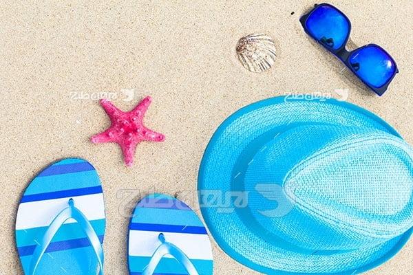 تصویر ساحل و شن و دمپایی کلاه و عینک