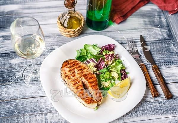غذای کباب گوشت ماهی و لیمو و سالاد و سبزیجات، چنگال و چاقو