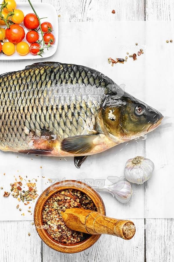 عکس ماهی تزئین شده و گوجه فرنگی و ادویه جات
