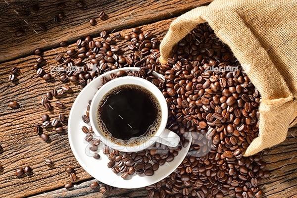عکس قهوه در فنجان سفید و دانه های قهوه