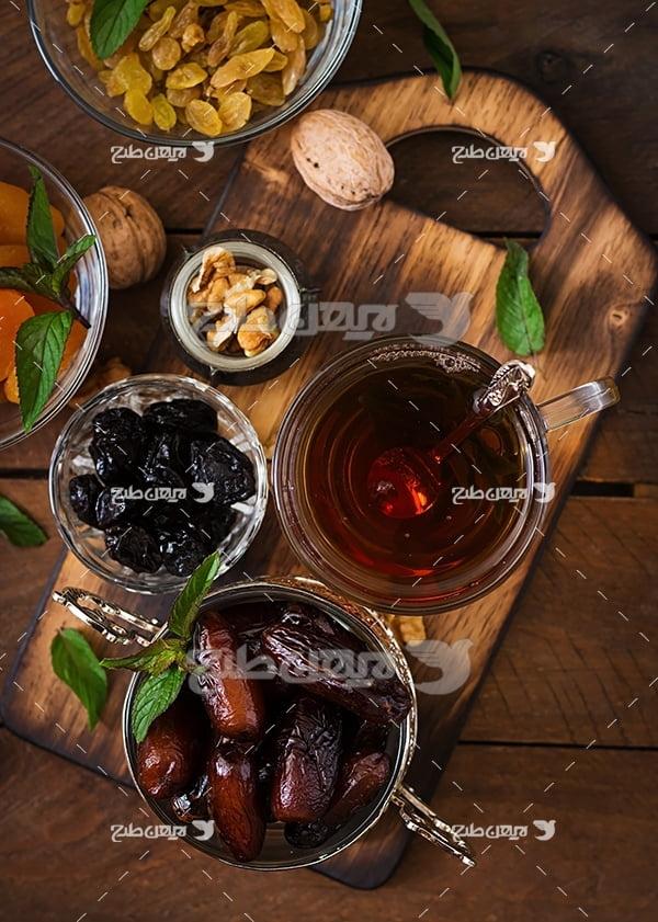 عکس استکان چای با خرما و گردو و کشمش