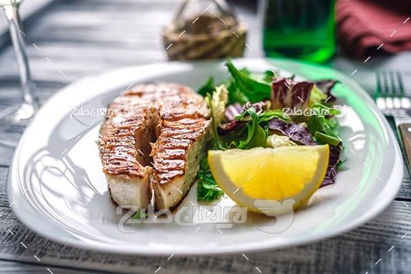 غذای کباب گوشت ماهی و لیمو و سالاد و سبزیجات، چنگال