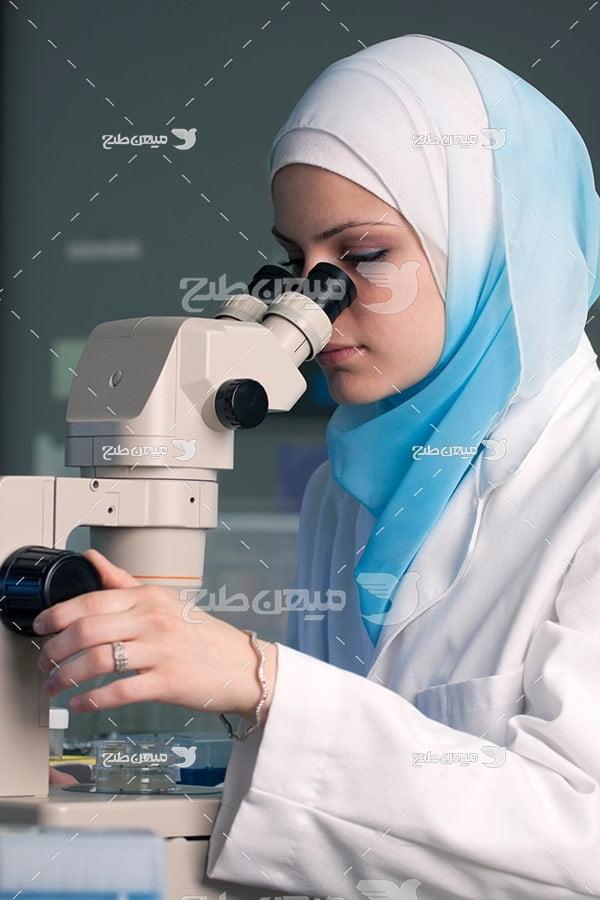 عکس تبلیغاتی پزشک خانم با حجاب و میکروسکوپ