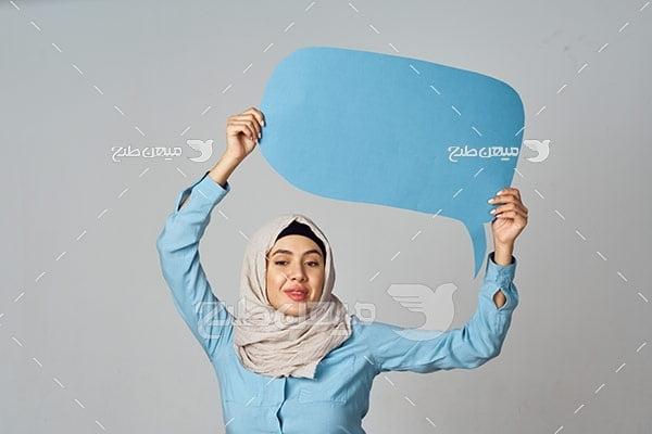 عکس زن با حجاب با یک بنر آبی