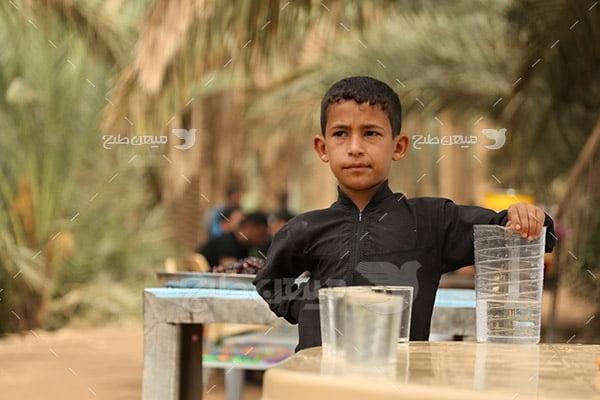 عکس کودک و آب صلواتی در پیاده روی اربعین حسینی